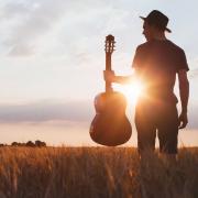 Man met gitaar tijdens zonsondergang