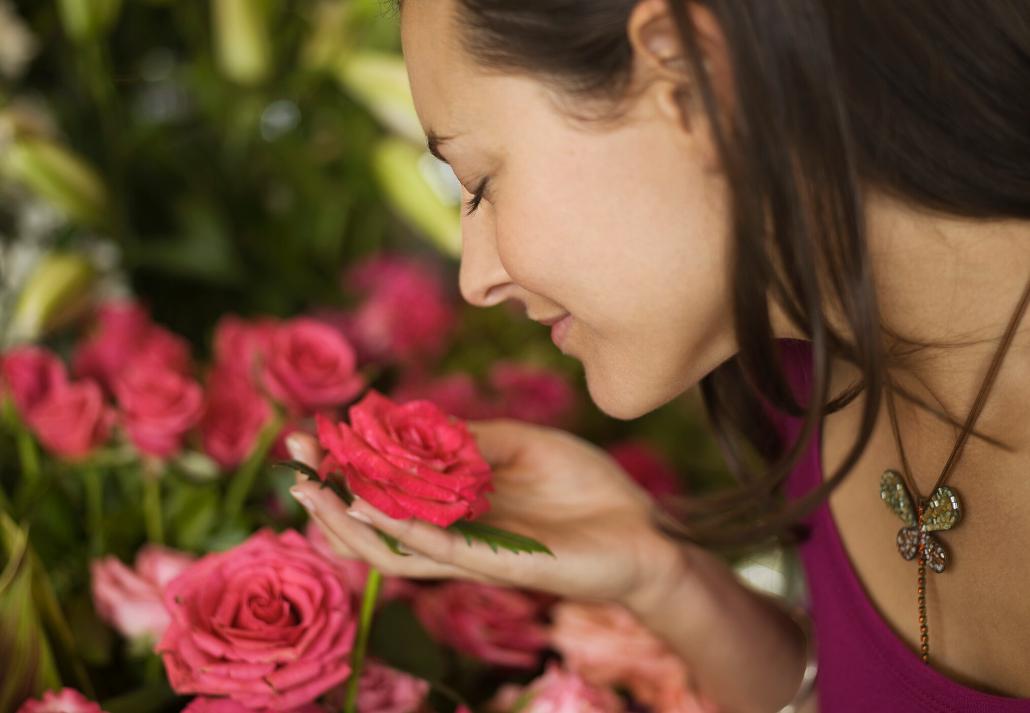 Vrouw ruikt aan geur van rozen