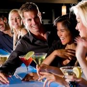 Mensen praten en lachen aan de bar onder het genot van drankjes en de juiste muziek